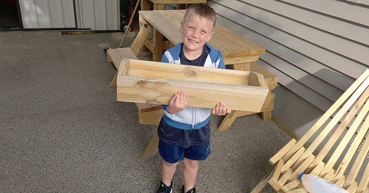 Young Carter holding a planter box he helped make